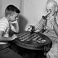 Boy Playing Checkers With Grandfather by Debrocke/ClassicStock