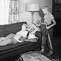 Boy With Baseball Vs. Napping Dad by D. Corson/ClassicStock