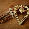 Braided Wicker Heart On Small Bundled Wood by Alexandre Fundone