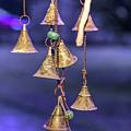 Brass Bells Hanging In The Illuminated Courtyard At Winter Night by Bratislav Stefanovic