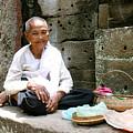 Buddhist Nun At Angkor Wat by John Meader