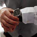 Businessman Looking At His Watch In Office by Jan Pavlovski
