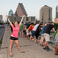 Cheerful Attractive Female Austinite Waves Her Hands With Excitement On Seeing The Austin Bats by Austin Bat Tours