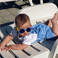 Child In A Denim Suit And Sunglasses Lying by Elena Saulich