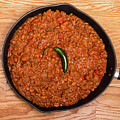 Chili In Black Pan On Wood Table With Jalapeno Pepper by Darryl Brooks