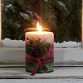 Christmas Candle Glowing On Window Sill With Snowy Evergreen Bra by Thomas Baker