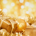 Christmas Scene With Gold Baubles And Gift On A Gold Background by Sara Winter