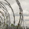 Coils Of Razor Wire On Fence by Karen Foley