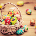 Colorful Hand Painted Easter Eggs In Basket And On Wood by Michal Bednarek