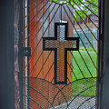 Cross On Church Door Open To Prison Yard With Light by Karen Foley