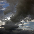 Dramatic Storm Clouds Against A Background Of Blue Sky by Christopher Purcell