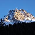 Fading Afternoon Sun Illuminates Mountain Peak  by Greg Hammond
