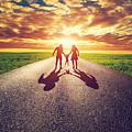 Family Walk On Long Straight Road Towards Sunset Sun by Michal Bednarek