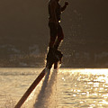 Flyboarder And Water Droplets Backlit At Sunset by Ndp