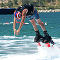 Flyboarder Bending Over To Dive Into Water by Ndp