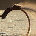 Flyboarder Doing Back Flip Over Backlit Waves by Ndp