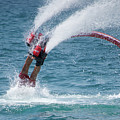 Flyboarder In Red Entering Water With Spray by Ndp