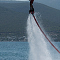Flyboarder In Silhouette Balancing High Above Water by Ndp