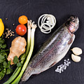 Fresh Whole Raw Fish And Herbs Displayed On Natural Slate Stone  by Thomas Baker