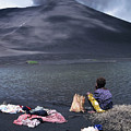 Girl Washing Clothes In A Lake With The Mount Yasur Volcano Emitting Smoke In The Background by Sami Sarkis