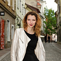Grinning Attractive Woman Standing On Cobblestone Street Of Uppe by Reimar Gaertner