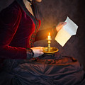 Historical Victorian Woman Reading A Letter By Candlelight by Lee Avison