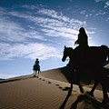 Horseback Riders In Silhouette On Sand by Axiom Photographic