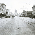 In This Historical 1913 Photo, Horse Drawn Carriages In Downtown Austin, Texas Run Up And Down Congress Avenue Cobblestone Streets Leading Up The The Texas State Capitol by Austin Welcome Center