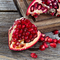 Juicy Ripe Pomegranates On Vintage Wood  by Thomas Baker