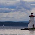Lighthouse And A Sail Boat In Nova Scotia by Sven Brogren