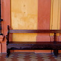 Long Wooden Bench Against A Yellow Wall At The Alcazar Of Seville by Sami Sarkis