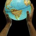 Man Holding Illuminated Earth Globe by Sami Sarkis