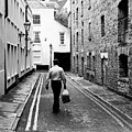 Man Walking With Shopping Bag Down Narrow English Street by Jacek Wojnarowski