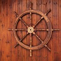 Nautical Wooden Ships Wheel On Wood Background by Vintage Nautical Art