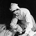 Nurse Tending To A Patient by Underwood Archives
