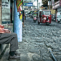 Old Man Sitting On An Cobblestone Street With Traffic Driving By by Sam Antonio Photography