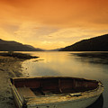 Old Rowboat At Waters Edge With Sunset by Don Hammond