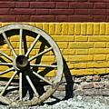 Old Wooden Wheel Against A Wall by Dan Radi