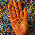 Orange Wooden Hand Holding Paperclips by Garry Gay