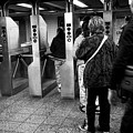 passengers moving through exit turnstiles in subway station New York City USA by Joe Fox