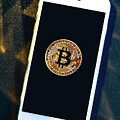 Phone With A Bitcoin Laying On Top Of It. by Michal Bednarek