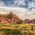 Photographer Waiting For The Badlands Light by Rikk Flohr