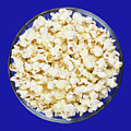 Popcorn In Glass Bowl On Blue Background by Peter Hermes Furian