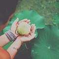 Portrait Of A Girl Holding Gently A Lotus Flower In Her Hands by Srdjan Kirtic