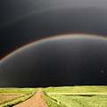Rainbow And Darkened Skies Seen Down A Country Road by Mark Duffy