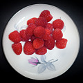 Raspberry On A Plate With Violet Flower by Alexander Fedin