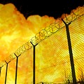 Realistic Orange Fire Explosion Behind Restricted Area Barbed Wire Fence, Blurred Background by Lukasz Szczepanski