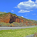 Red Cliffs And White Clouds Over Interstate 80 Rest Stop In Utah  by Ruth Hager