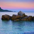 Sand Rocks In The Sea At Sunset by Goran Kojadinovic