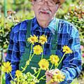 Senior Gardener Showing A Potted Flower. by Michal Bednarek